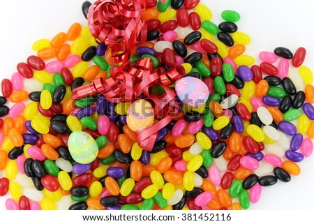 Mound of Jelly Beans with Small Easter Eggs and Red Ribbon - stock photo