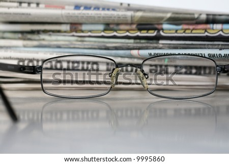 Mound of newspapers and glasses - stock photo