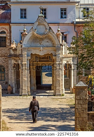 MOUNT ATHOS - MAY 22, 2014: Monk in black robe entering St. Andrew's Skete on Holy Mount Athos.  The Russian Skete of Saint Andrew is located not far from Karyes belongs to the Monastery of Vatopedi. - stock photo