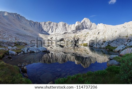 Mount Carl Heller reflected in an alpine lake in the Sierra Nevada Mountains of California - stock photo