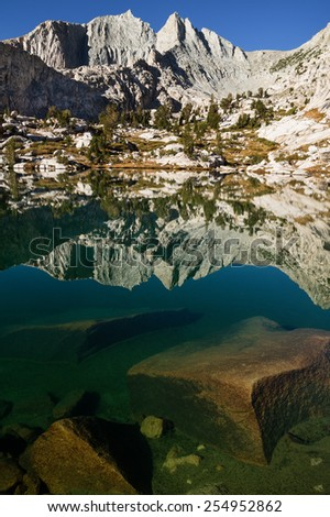 Mount Cotter reflected in a clear lake in the Sixty Lakes Basin of Kings Canyon National Park California - stock photo