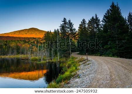 Mount Deception reflecting in a pond along a dirt road in White Mountain National Forest, New Hampshire. - stock photo