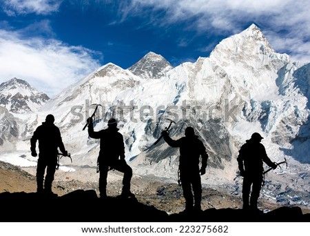 Mount Everest and silhouette of men - trek to everest base camp - Nepal - stock photo