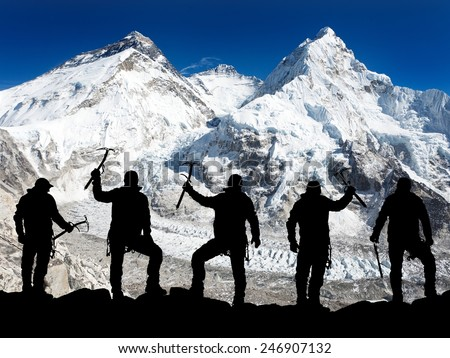 Mount Everest from Pumo Ri base camp and silhouette of men - trek to everest base camp - Nepal  - stock photo