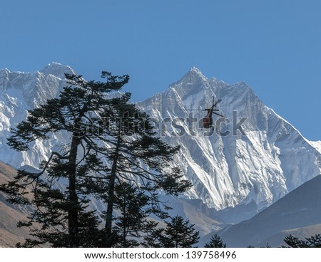 Mount Everest (8848 m) and Lhotse (8511 m) with helicopter (view from Tengboche monastery) - Nepal, Himalayas - stock photo
