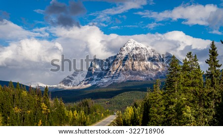 Mount Fitzwilliam traveling east on the Yellowhead Highway,  part of the Canadian Rockies. The lower half is dolomite. The upper half quartzite covered with lichen and gives it a very dark gray color. - stock photo