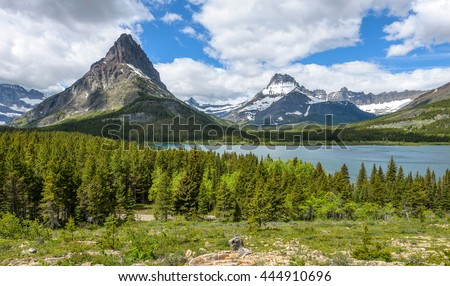 Mount Grinnell and Mount Wilbur - A panoramic spring view of Mount Grinnell and Mount Wilbur rising high above Swiftcurrent Lake  in Many Glacier region of Glacier National Park, Montana, USA. - stock photo