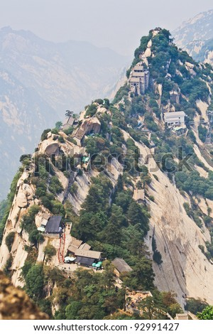"""Mount Hua,located in Shaanxi,is the highest of China's five sacred mountains, called the """"West Mountain"""",well known for steep trails, breath-taking cliffs, narrow passages, and grand scenery. - stock photo"""