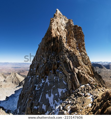 Mount Humphreys summit spire in the Sierra Nevada Mountains with two mountaineers at the base - stock photo