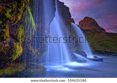 Mount Kirkjufell (Church mountain) in the Snaefellsnes peninsula, Iceland (Island), complimented by a waterfall on a beautiful summer evening - stock photo