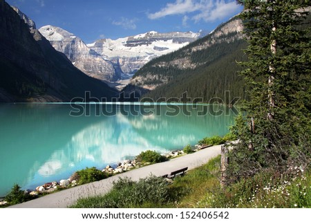 Mount Lefroy (left) Mount Victoria (center), Lake Louise, Banff National Park, Alberta, Canada.  Pathway leads around Lake Louise and to the Plains of Six Glaciers Tea House. - stock photo