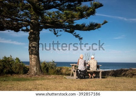 MOUNT MAUNGANUI BEACH,  TAURANGA, NEW ZEALAND - JANUARY 7; An elderly couple relax with ice creams at the beach on January 7, 2015 at Mount Maunganui near Tauranga, New Zealand.    - stock photo
