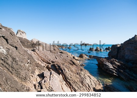 Mount Maunganui, rocky coastline crevasse between two formations with water flowing in. - stock photo