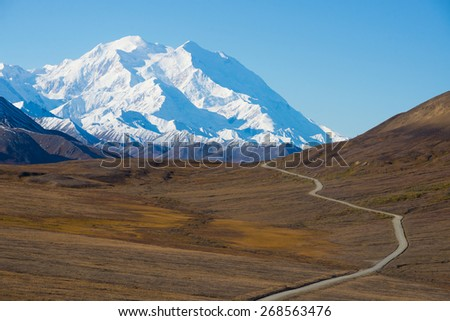 Mount McKinley's snowy peak with the park road and tundra in the foreground, Denali National Park, Alaska, US. Mount McKinley is the highest peak in North America.