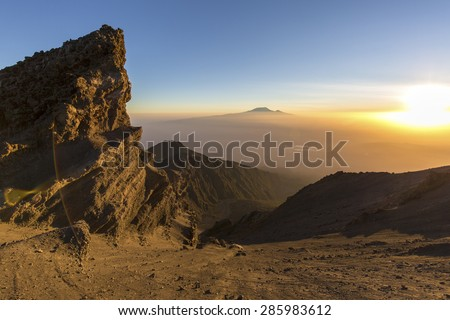 Mount Meru and Mt Kilimanjaro in the distance near Arusha in Tanzania. Africa. Mt Meru is located 60 kilometres west of Mount Kilimanjaro. - stock photo