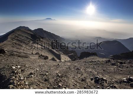 Mount Meru with Mt Kilimanjaro in the distance near Arusha in Tanzania. Africa. Mt Meru is located 60 kilometres west of Mount Kilimanjaro. - stock photo