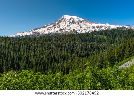 Mount Rainier towers over the surrounding mountains - stock photo