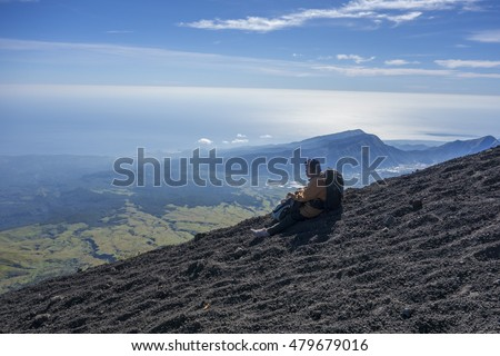 MOUNT RINJANI, LOMBOK, INDONESIA - JUNE 13, 2015 : Unidentified mountaineer takes a rest after reached the peak. Rijani mountain is one of the highest mountains in Indonesia