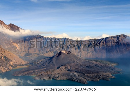 Mount Rinjani volcano and volcanic cone in a cloud covered crater lake in Asia