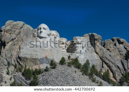 Mount Rushmore set against a bright cloud free blue sky.