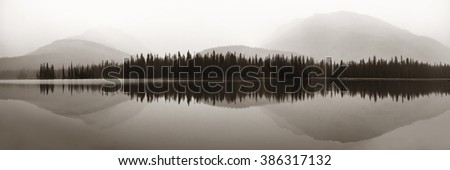 Mountain and forest over lake with reflections in a foggy day. - stock photo