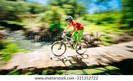 Mountain Bike cyclist riding track at sunny day, healthy lifestyle active athlete doing sport. Abstract Background - stock photo