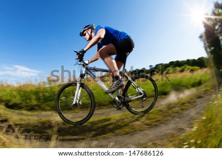 Mountain bike downhill on country road - stock photo