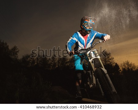 Mountain bike evening. Downhill biking. Portrait of a professional cyclist in the helmet. MTB. Concept about people and sport. - stock photo