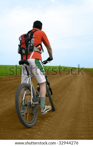 mountain bike race on ground road in the field. - stock photo