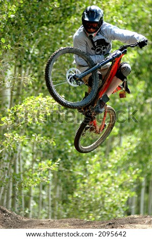 mountain bike racer in mid flight - stock photo
