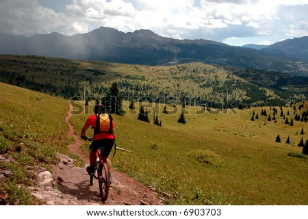 mountain bike rider on single track trail in the Rocky Mountains with storm in distance - stock photo