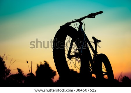 mountain bike silhouette beautiful sunset, silhouette fat bike add filter vintage color - stock photo