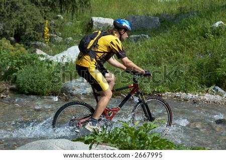 Mountain biker and creek - stock photo