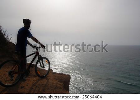 mountain biker by the ocean silhouette - stock photo