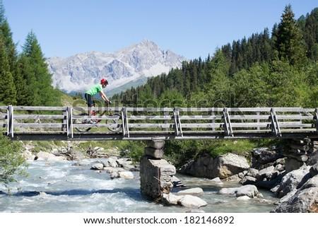 Mountain biker crossing wooden bridge in Swiss mountain area of Graubunden - stock photo