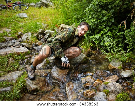 Mountain Biker drinking water from a stream