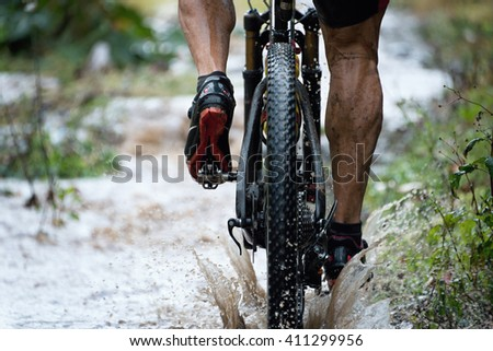 Mountain biker driving in rain upstream creek - stock photo