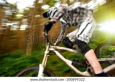 Mountain biker going fast downhill with speed blur and trees in the background - stock photo
