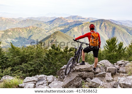 Mountain biker looking at view on bike trail in autumn mountains. Rider cycling on rocky single track. Sport fitness motivation and  adventure inspiration. - stock photo