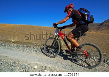 Mountain biker on old road in desert - stock photo