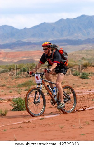 Mountain biker racing in desert mountains - stock photo