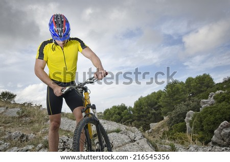 Mountain biker resting near to his bicycle - stock photo
