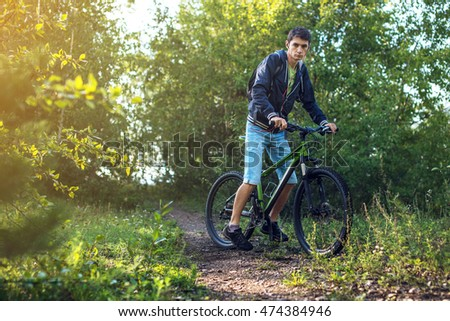 Mountain biker rides a Bicycle in the morning on a country road.