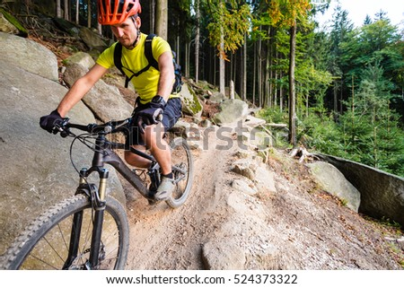 Mountain biker riding on bike in autumn inspirational mountains landscape. Man cycling MTB on enduro trail track. Sport fitness motivation and inspiration. Fitness and exercising in fall outdoors.
