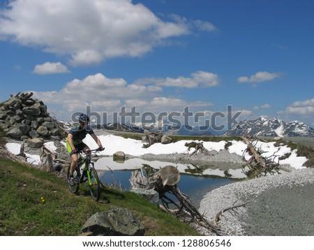 Mountain biker riding through the mountains - stock photo
