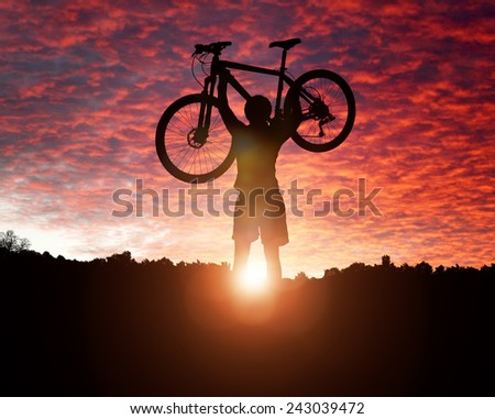 Mountain biker silhouette against the sunset concept for achievement, conquering adversity and  exercising - stock photo