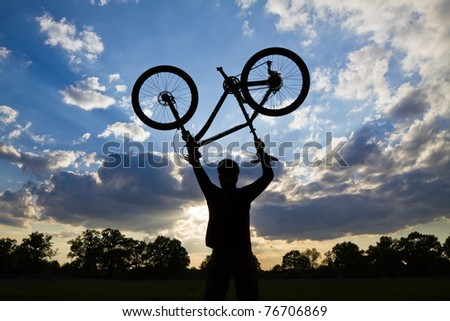 Mountain biker silhouette in summer over blue sunset sky, cycling and success concept - stock photo
