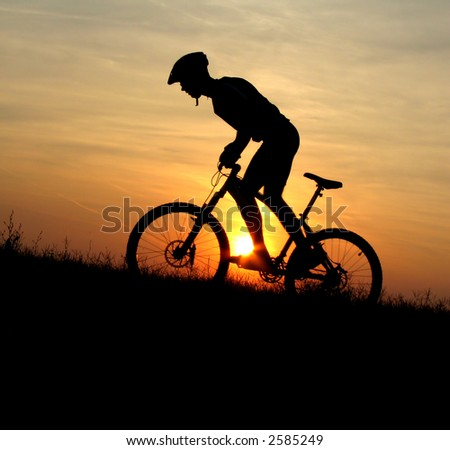 mountain biker silhouette in sunrise - stock photo