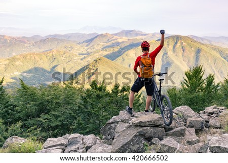 Mountain biker success, looking at view on bike trail in autumn mountains. Successful happy rider on rocks. Business concept. Sport adventure motivation and inspiration outdoors.