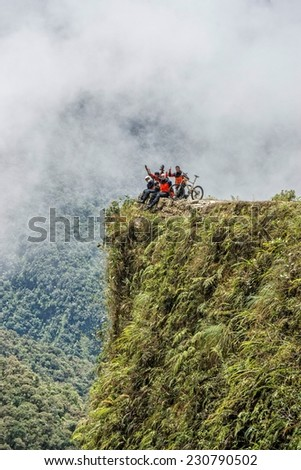"Mountain bikers are posing at a viewpoint of the famous downhill trail ""Road of death"" in Bolivia - stock photo"